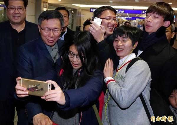 台北市長柯文哲(左二)結束赴日考察行程30日晚間搭機返抵桃園機場,旅客爭相與柯市長自拍合影。(記者朱沛雄攝)