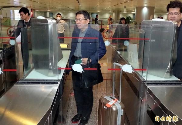 台北市長柯文哲(中)結束赴日考察行程30日晚間搭機返抵桃園機場,自己拖著隨身行李使用自動通關入境。(記者朱沛雄攝)
