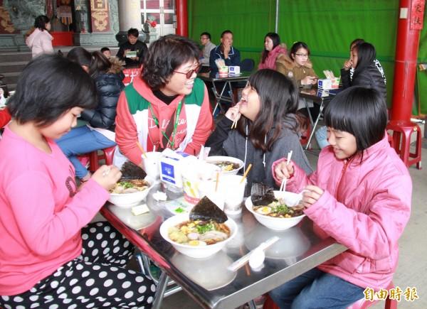 家扶童第一次吃到拉麵,興奮的跟督導林惠媚說,好好吃,好幸福。(記者陳冠備攝)