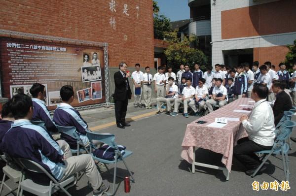 雄中學聯會在斑駁彈痕的紅磚牆前辦228活動。(記者方志賢攝)