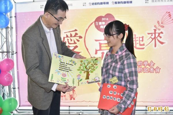 受助學生製作樹木茁壯的卡片感謝慶聯港都有線電視董事長黃建全(左)。 (記者張忠義攝)