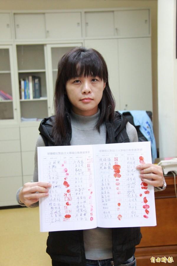 埔鹽鄉代會主席許文萍出示反火化場自救會連署書簽名。(記者陳冠備攝)