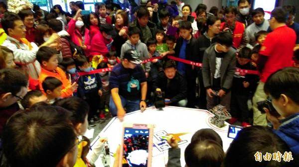 「機器人格鬥闖關體驗賽」,吸引大小朋友圍觀,觀眾情緒跟著戰事起伏,相當精采。(記者何玉華攝)