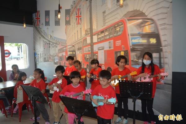 倫敦餐館以英國地鐵站為主題,孩子們在地鐵站布幕前拉起烏克麗麗,就像是在英國街頭表演,有著異國風情。(記者游明金攝)