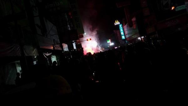 大甲媽祖鑾轎今天凌晨行經彰化市三民路時,突然有人點燃信號彈丟擲,現場火光四射。(讀者提供)