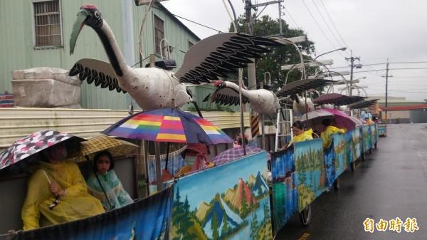 七鶴陣神童穿雨衣拿雨傘避雨。(記者楊金城攝)