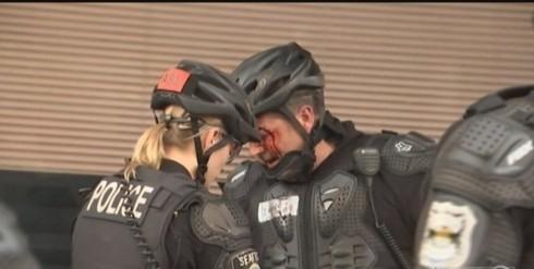 一名警察被汽油彈的玻璃瓶砸中,滿臉鮮血。(圖擷自推特)