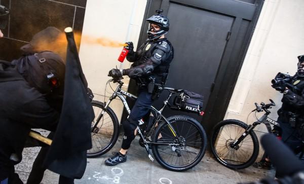 警察使用胡椒噴霧對付滋事份子。(美聯社)