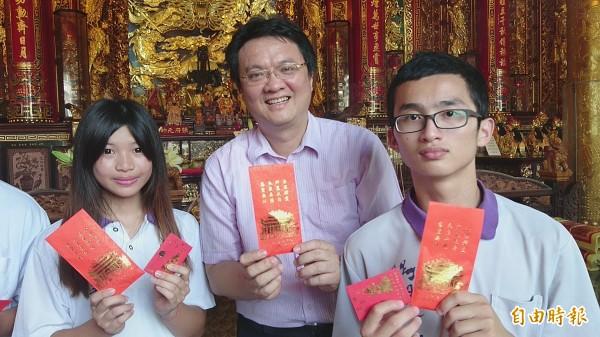 慈聖宮主委陳俊銘(中)送給內有1元和稻穀的祈福紅包給完成成年禮的學生。(記者楊金城攝)