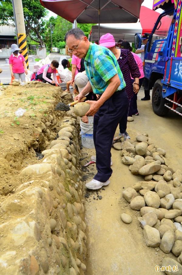 志工們進行漿砌卵石的修補,為日治時期的防空洞善後。(記者吳俊鋒攝)