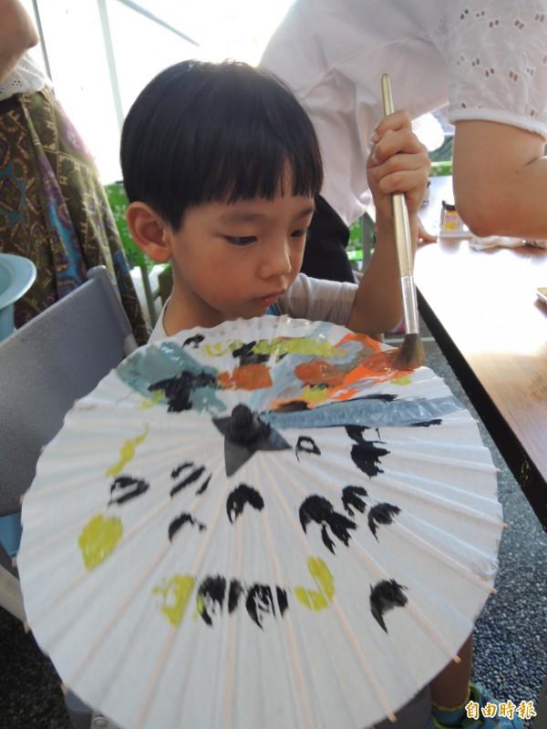 水萍塭公園舉辦「南客市集」,小朋友專注彩繪客家小紙傘。(記者洪瑞琴攝)