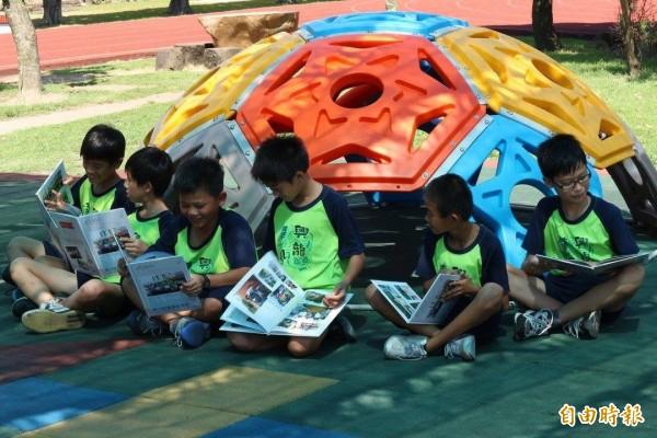 彰化二林興華國小學生,開心的翻閱新的畢業紀念冊。(記者陳冠備攝)