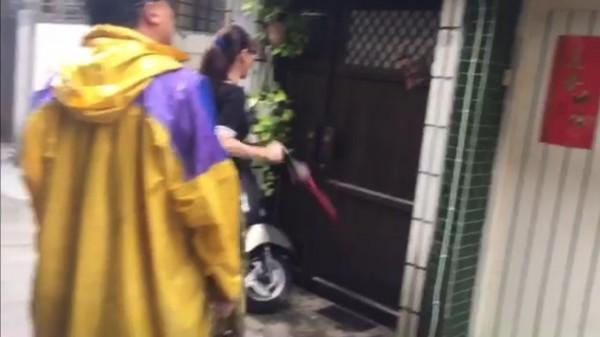 女子持雨傘猛戳洪家門。(記者方志賢翻攝)
