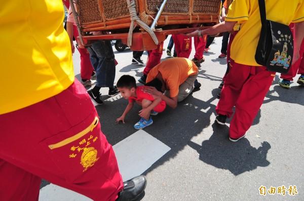 男子與男童一起鑽轎底,祈求平安。(記者李忠憲攝)