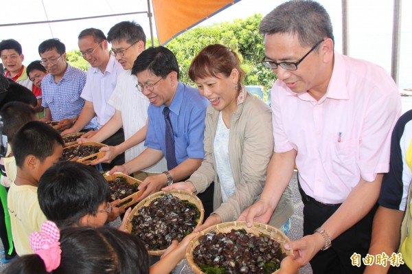 福連國小學童接過九孔幼苗,象徵海洋教育傳承。(記者林欣漢攝)