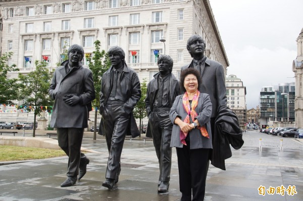 花媽在利物浦市府(後面大樓)外,與披頭四雕像合影。(記者王榮祥攝)