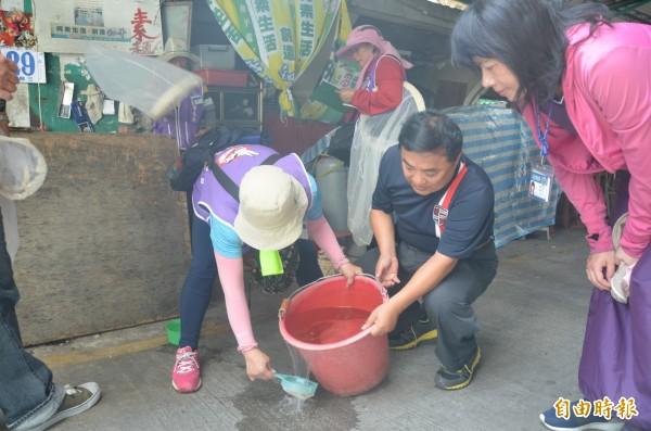 衛生局人員正在檢查積水容器及孳生源情況(記者葉永騫攝)