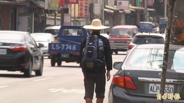 實在太熱了,外出民眾在新屋街頭以衣物、打傘遮陽或是狂喝水、涼茶消暑。(記者李容萍攝)