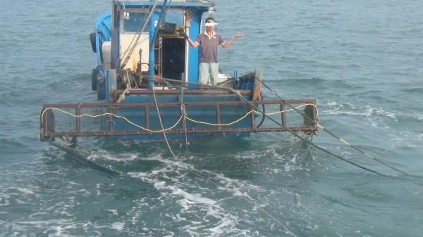 被金門海巡隊查獲的中國漁民,雙手一攤表示「聽不到」。(圖由金門海巡隊提供)