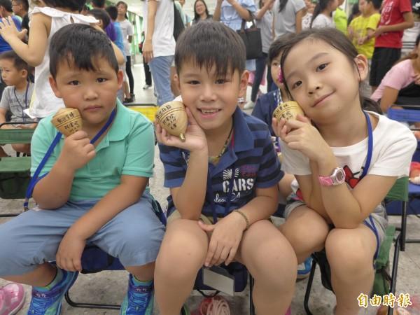 八里區米倉國小開學,新生喜獲陀螺,學童們愛不釋手。(記者李雅雯攝)