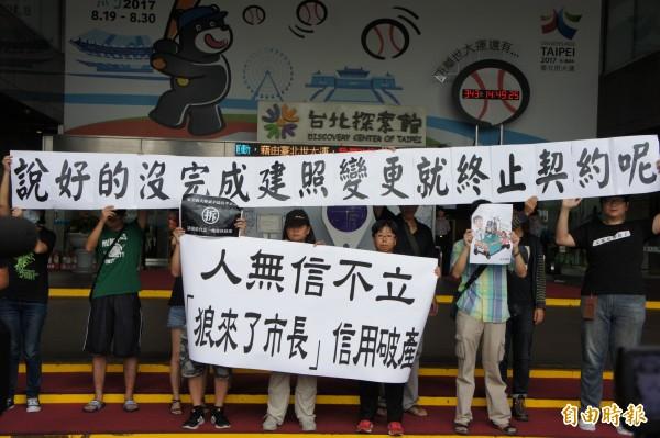 公民團體今天上午聚集北市政府門口,高舉標語痛斥柯市府遭財團綁架。(記者黃建豪攝)