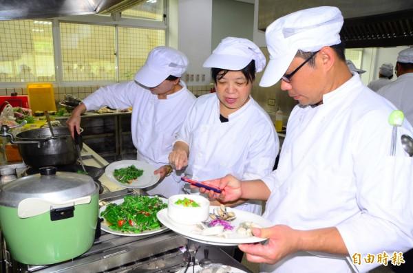 地方小吃培訓班的學員,現場料理傳統美食,不時參考手機上的筆記,讓作品更完美。(記者吳俊鋒攝)