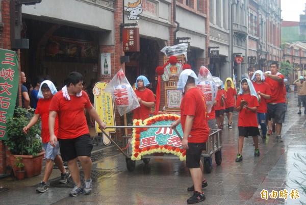 三峽傳統習俗「迎尪公」,即使颱風侵襲,轎班仍不畏風雨繞境至三峽老街。(記者張安蕎攝)