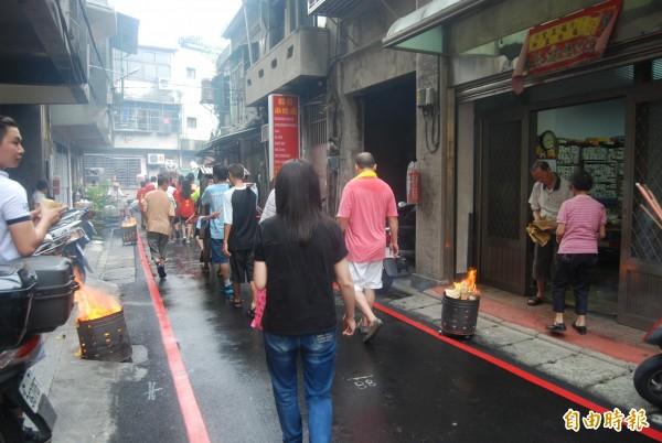 三峽「迎尪公」繞境至街頭小巷內,家家戶戶擺起香案、燒紙錢迎神。(記者張安蕎攝)