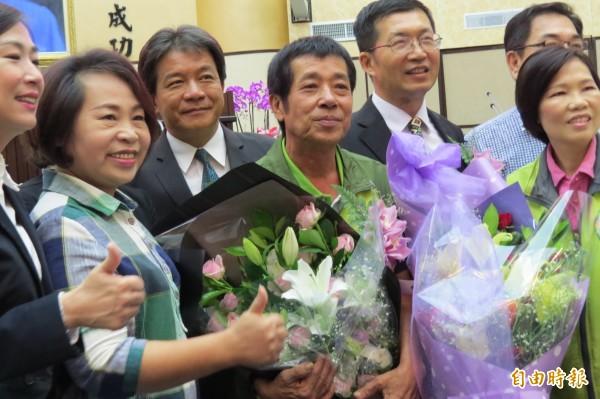 王峻潭(中)遞補宣誓就職後,議會同仁送花道賀。(記者蔡文居攝)