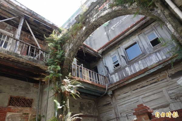 歷史建築鹿港十宜樓的天井2樓通道圓木、通道磚造排水溝的原有樣貌,另一側仍保存良好。(記者劉曉欣攝)