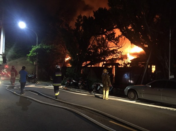 台北市金華街一排日式平房凌晨突然竄出火舌,烈焰沖天,消防員趕緊佈水線滅火。(記者姚岳宏翻攝)