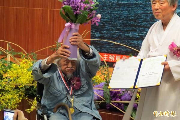 史明獲頒「杏花村文化貢獻獎」,他高舉花束向大家致意。(記者蔡文居攝)