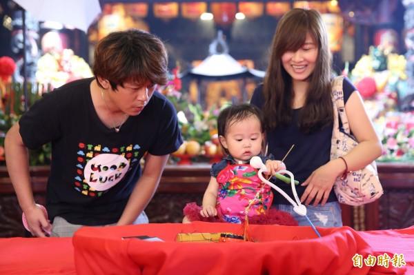 福興宮今舉辦抓周,許多家長看到寶寶抓到的吉祥物笑得好開心。(記者陳燦坤攝)