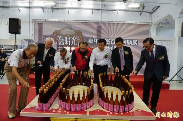 台中舊酒廠曾是全台最大的米酒廠,今慶祝百歲生日,文化局官員、立委和酒廠耆老點紅標米酒蠟燭慶祝。(記者蔡淑媛攝)