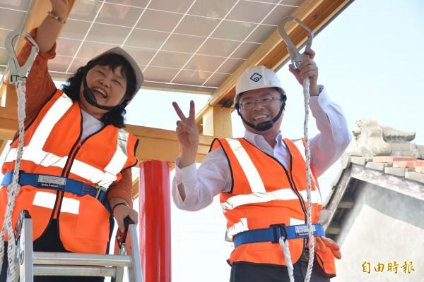 立委洪宗熠(右)、陳曼麗(左)爬上鷹架裝置太陽能板。(記者陳冠備攝)