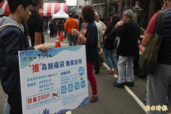 民眾大排長龍搶購市價八折的九孔福袋。(記者林欣漢攝)