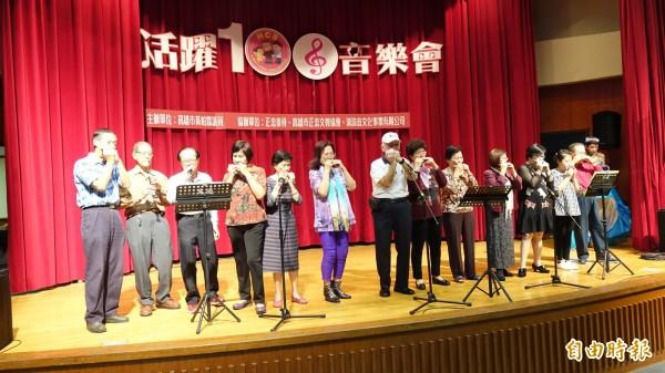 台灣全人關懷照護服務協會發動互助孫帶長輩彈唱吹奏,並與長輩歌舞同樂。 (記者張忠義攝)