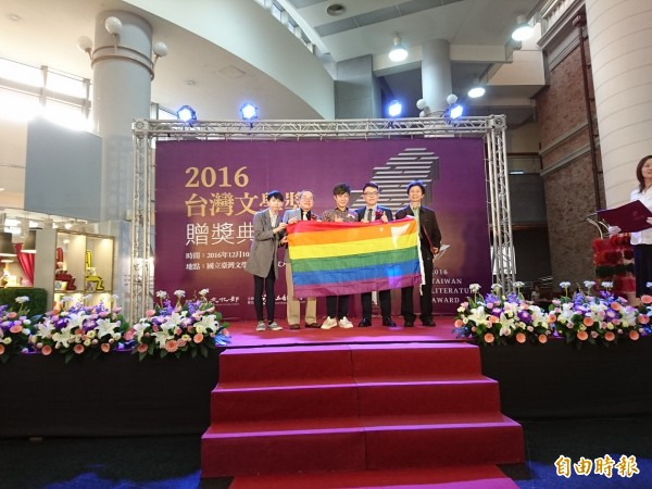 台灣文學獎頒獎典禮,陳栢青(中)舉彩虹旗上台領獎。(記者洪瑞琴攝)