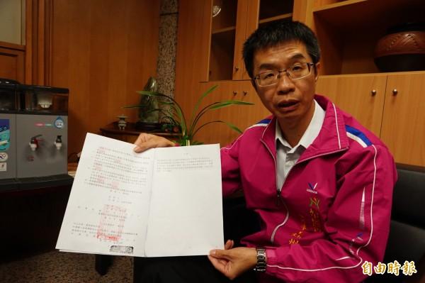 后里區農會總幹事王鈺州拿出法院判決表示,公告內容及大小皆依法院判決規定。(記者歐素美攝)