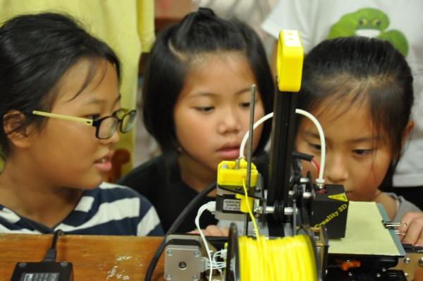 崇倫國中機器人社將3D列印課程帶至南投縣溪南國小,小學生們對3D列印非常好奇,專注地看著3D印表機上的作品。(黃忠志提供)