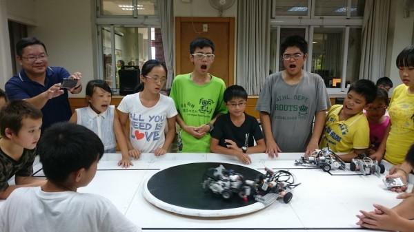 場中正激烈進行相撲機器人大賽,讓小朋友緊張到巴都合不起來了。(黃忠志提供)