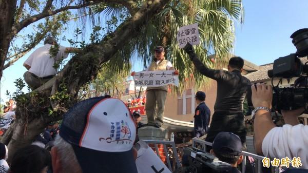 下一代幸福聯盟成員,爬入立法院圍牆後,被警方逮捕,其他民眾在外面高喊「打開大門,公民進入」,並要求讓律師進入協商。(記者陳炳宏攝)