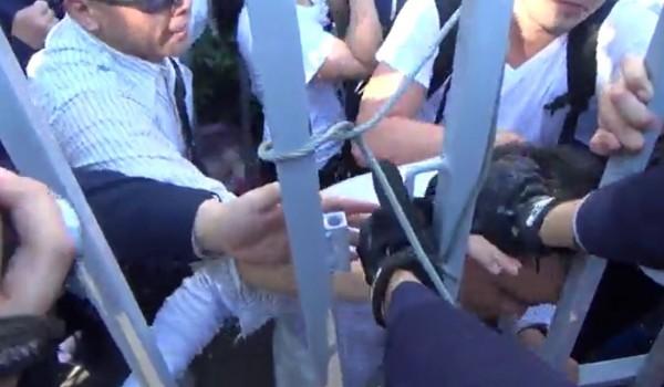 龍幸抗議者以頭部自撞立院鐵欄杆,警方多次伸手阻擋。(圖由警方提供)