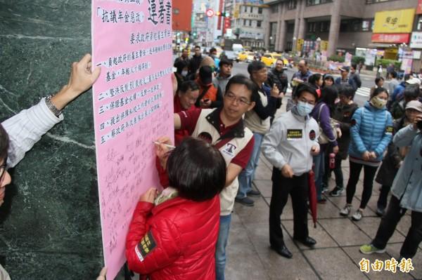 教師們簽署連署書抗議年金改革。(記者林欣漢攝)