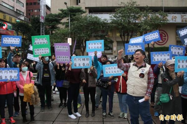教師們高舉標語抗議年金改革。(記者林欣漢攝)