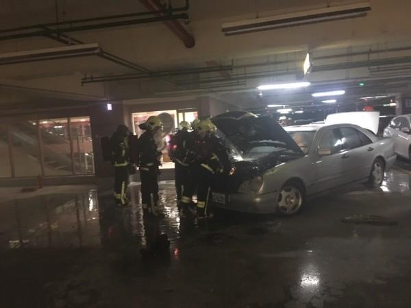 雙B名車倒車時,引擎突然冒煙起火,警消趕赴撲滅。(記者陳薏云翻攝)