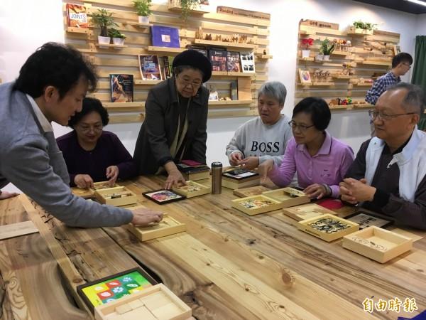 信誼基金會推出長者手作「人生記憶寶盒」的木作課程,一群長者專注地聆聽老師的說明。(記者林曉雲攝)