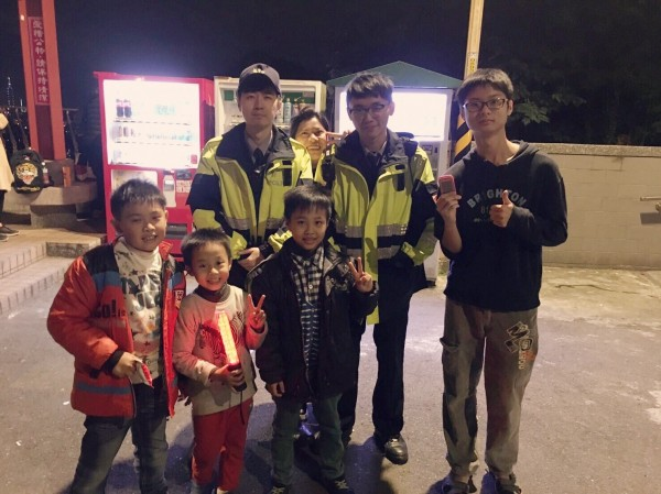 員警陪著左方撿到手機的3名孩子,找到手機的主人右方著黑衣的曾姓男子。(記者徐聖倫翻攝)