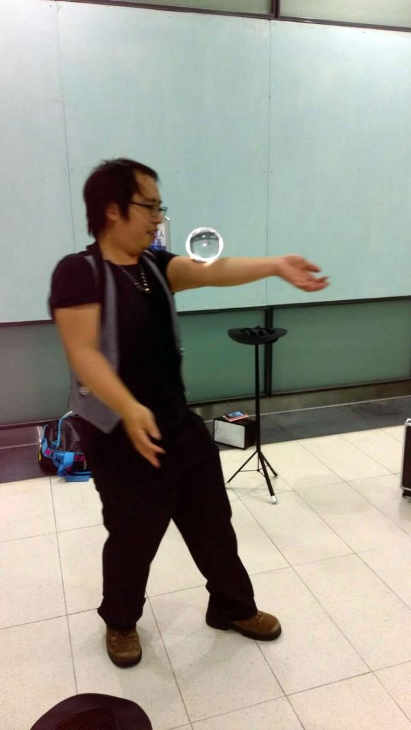街頭藝人周君翰在機捷站表演水晶球魔術,讓試乘旅客目不轉睛。(桃捷公司提供)