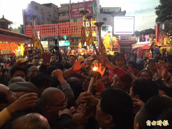 媽祖元神平安燈一出廟外,信眾立刻包圍用手過火祈福。(記者李忠憲攝)